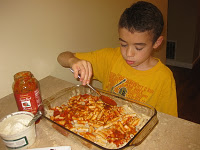 """Step 1: Spread the penne pasta in a 9X13 glass pyrex dish. Have the kiddies spoon pasta sauce evenly over the penne. If they are working on the /l/ sound, have them practice the sound /l/, syllable /la/ as in """"lah"""" or word """"lasagna""""as they spread the sauce"""